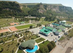 Деревянная беседка с мангалом на берегу озера и горы. Отель Адиюх-Пэлас, Хабез, Карачаево-Черкессия.